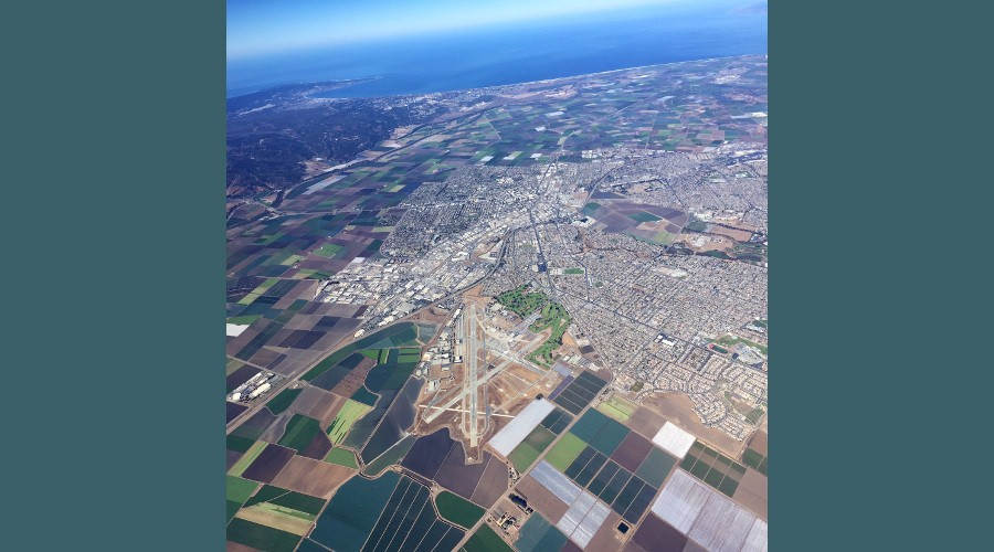 Salinas Airport seen from an airplane, surrounded by city, farmland, and Monterey Bay