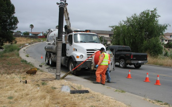 City workers pumping sewage from manhole by a sidewalk